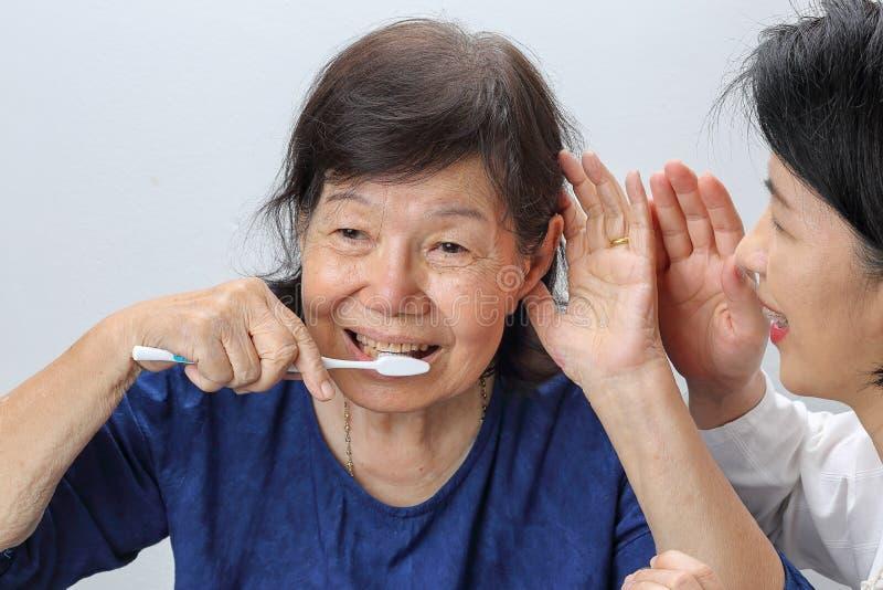 Asiatisk förlust för pensionärkvinnautfrågning som är lomhörd royaltyfri fotografi