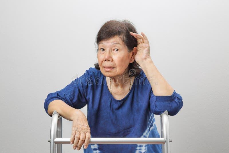 Asiatisk förlust för pensionärkvinnautfrågning som är lomhörd fotografering för bildbyråer