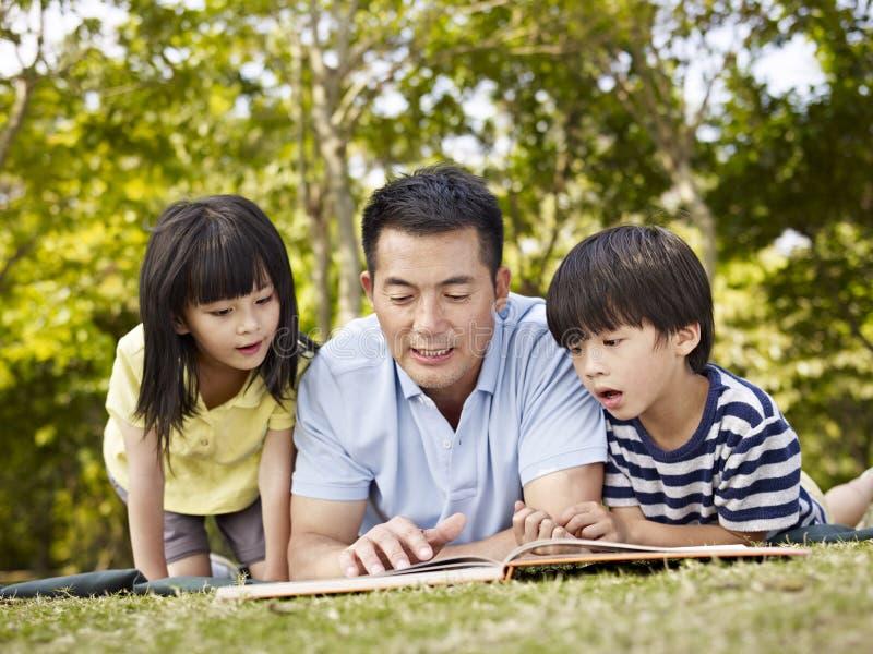 Asiatisk fader och barnläsebok tillsammans royaltyfria foton