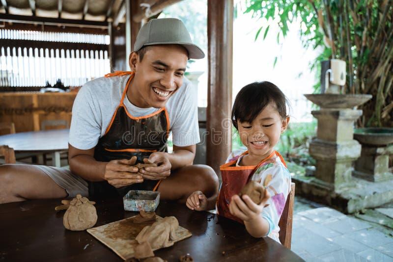 Asiatisk fader och dotter som arbetar med lera royaltyfria bilder