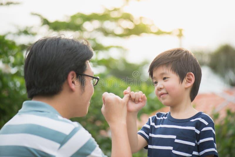 Asiatisk fader och hans son som gör en lillfinger att lova royaltyfria foton