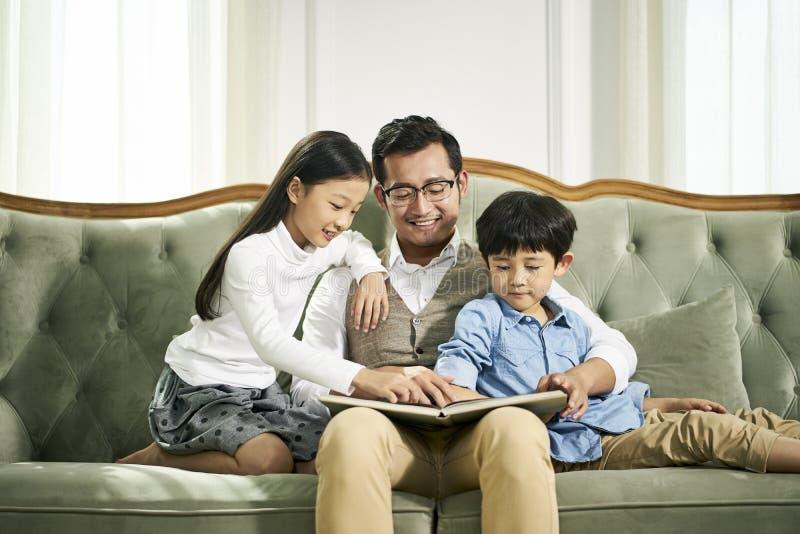 Asiatisk fader och läsebok för två barn tillsammans arkivfoto