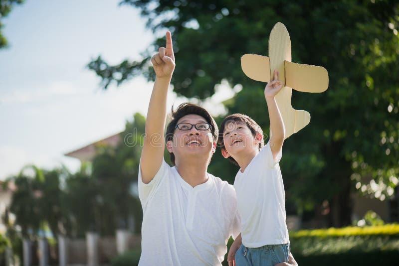 Asiatisk fader och son som spelar pappflygplanet tillsammans fotografering för bildbyråer