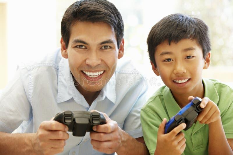 Asiatisk fader och son som spelar videogames arkivbild