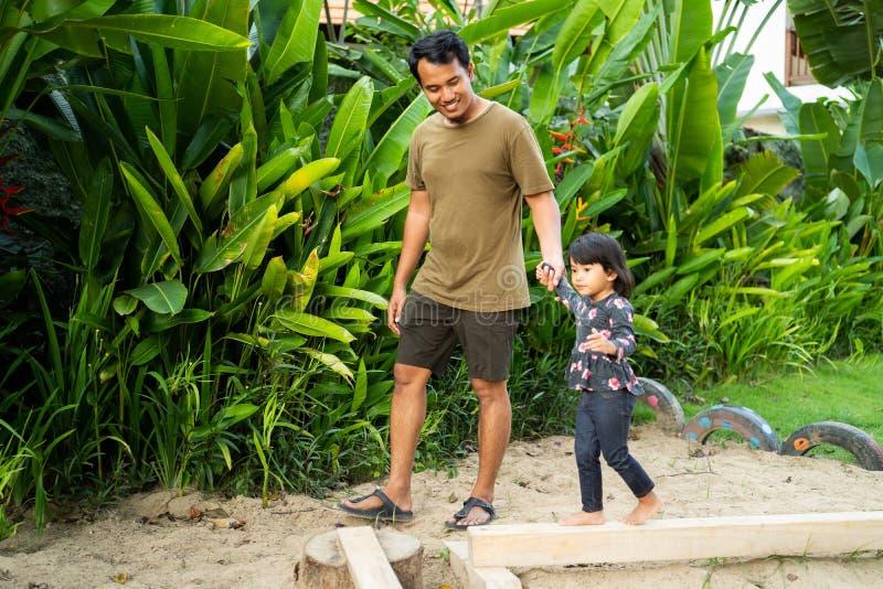 Asiatisk fader som rymmer händer för en dotter, när spela balansbommen arkivfoto