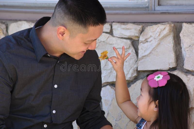 Asiatisk fader som spelar med den unga dottern utanför arkivbild