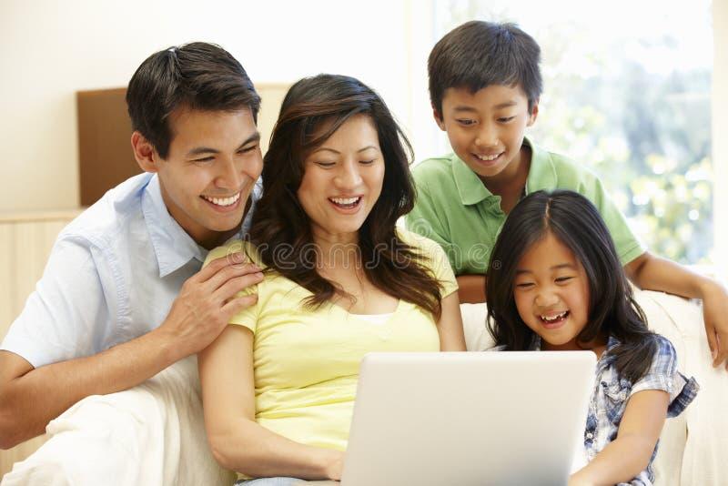 Asiatisk familj med bärbara datorn royaltyfria bilder