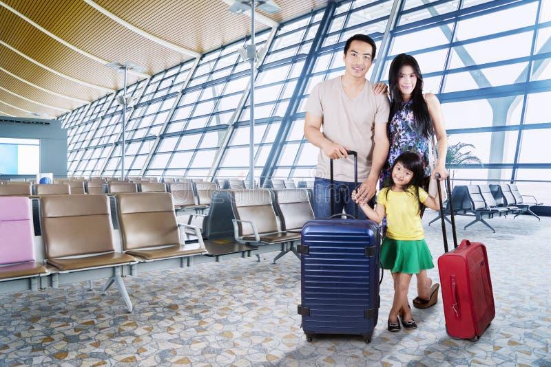 Asiatisk familj med resväskor på flygplatsen fotografering för bildbyråer
