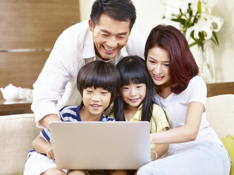Asiatisk familj med två barn som tillsammans använder bärbara datorn arkivbilder
