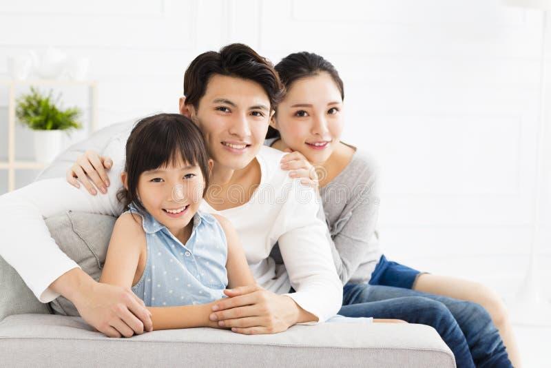 Asiatisk familj på soffan i vardagsrum royaltyfri fotografi
