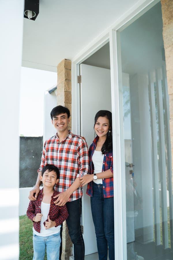 Asiatisk familj som är främst av dörren av deras hus arkivfoto