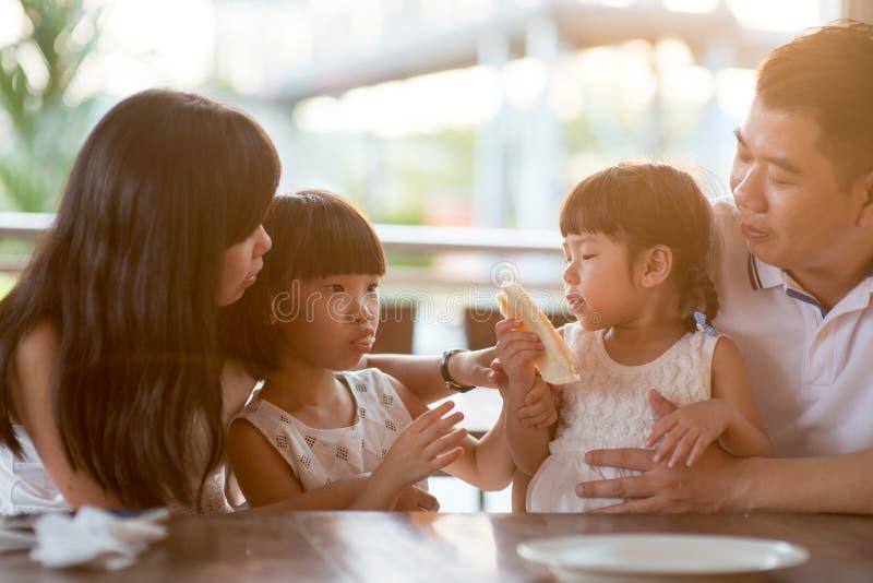 Asiatisk familj som äter mat på kafét arkivbild
