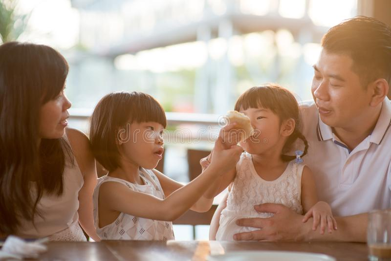 Asiatisk familj som äter på kafét royaltyfria bilder