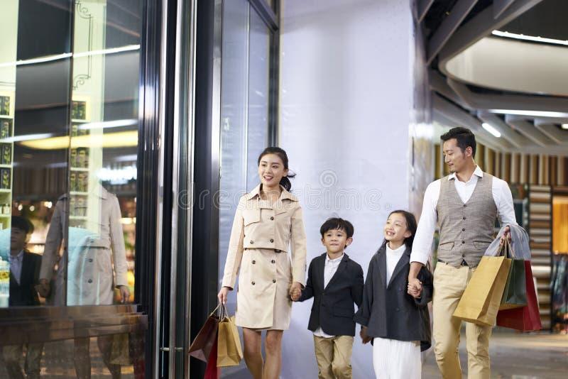 Asiatisk familj som går i shoppinggalleria fotografering för bildbyråer