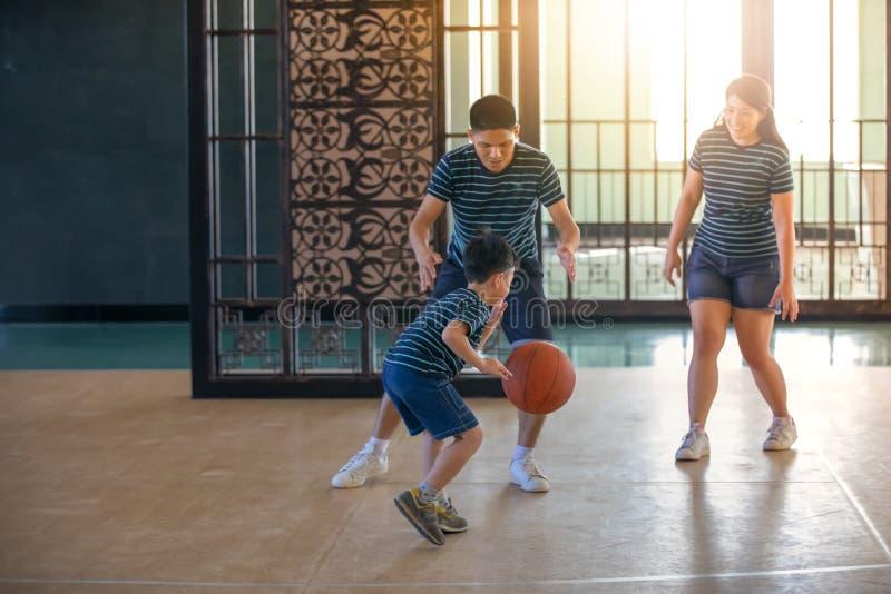 Asiatisk familj som spelar basket tillsammans Lycklig familjutgifter arkivbild