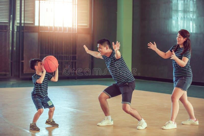 Asiatisk familj som spelar basket tillsammans Lycklig familj som tillsammans spenderar fri tid på ferie arkivfoto