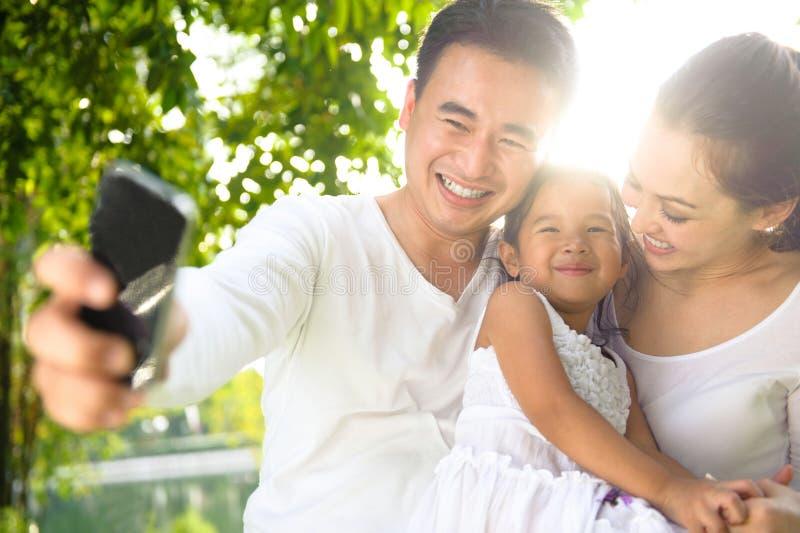 Asiatisk familj som tar fotografier arkivbilder