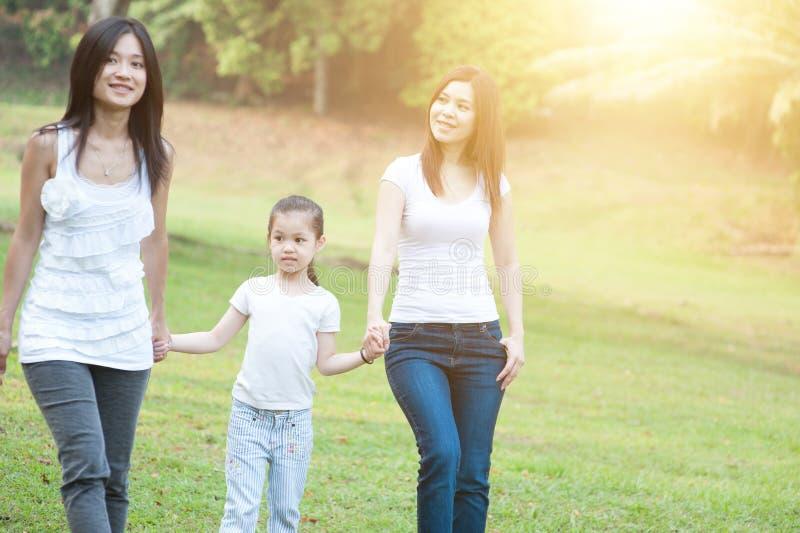 Asiatisk familj som utomhus går royaltyfri fotografi
