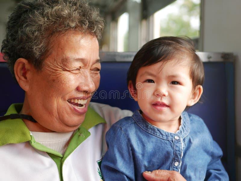 Asiatisk farmor som skrattar och ler, medan tycka om rymma hennes sondotter som dem som tillsammans reser på ett drev royaltyfri fotografi