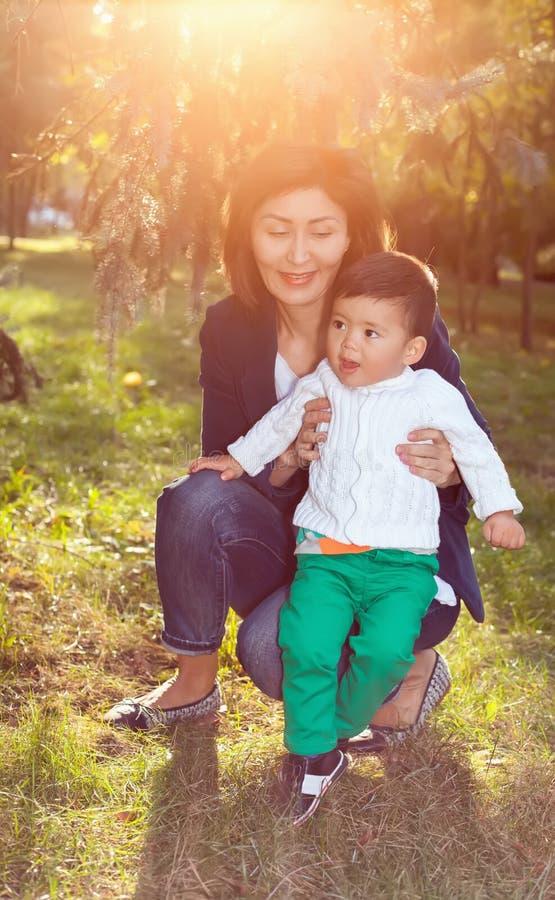 Asiatisk farmor som spelar med hennes sonson i parkera arkivfoton