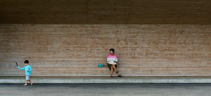 Asiatisk farmorkvinna som håller ögonen på hennes sonson att gå omkring och spela med en fjäder arkivfoto