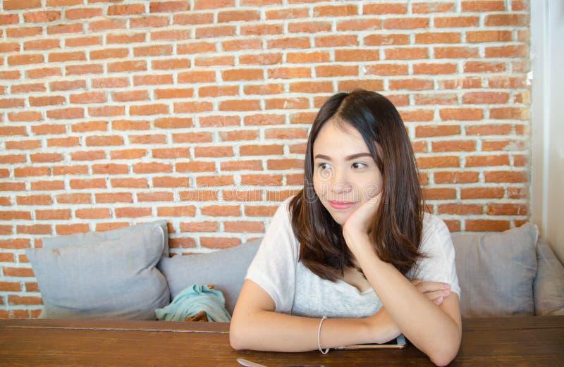 Asiatisk flicka att vila ens haka på ens händer fotografering för bildbyråer