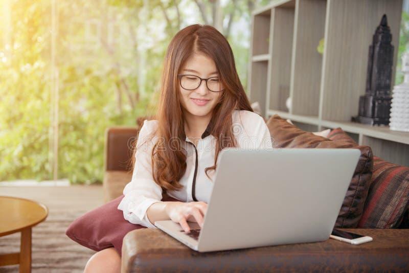 Asiatisk flicka för affär som lutar och använder en bärbar dator i arkiv royaltyfri bild