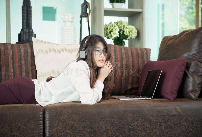 Asiatisk flicka för affär som lutar och använder en bärbar dator på soffan, person fotografering för bildbyråer