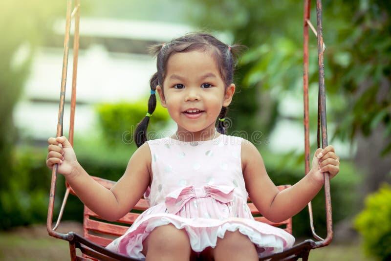 Asiatisk flicka för barn som har gyckel som spelar gunga i lekplats arkivfoton