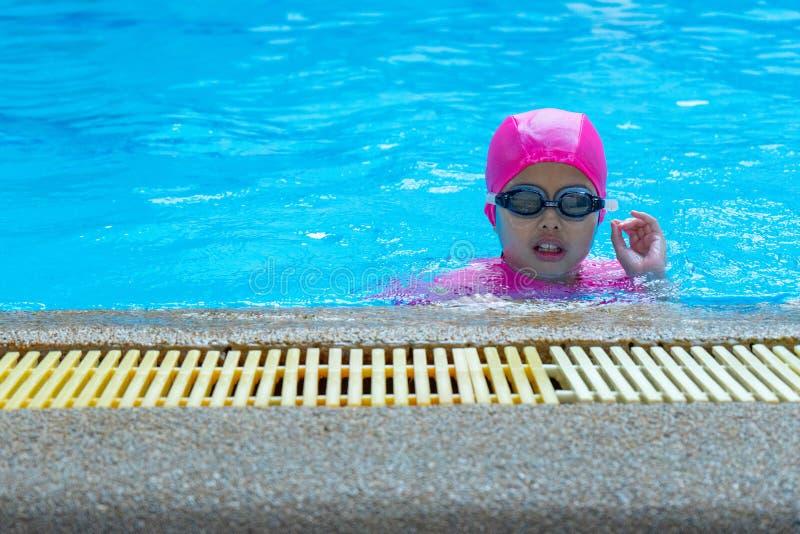Asiatisk flicka för Closeupstående med att simma följet och glasögon i pölen arkivbild