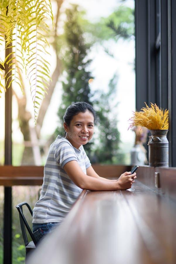 Asiatisk flicka för foto som ser kameran i coffee shop fotografering för bildbyråer
