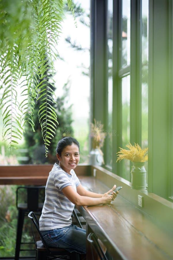 Asiatisk flicka för foto som ser kameran i coffee shop arkivfoton