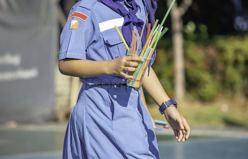Asiatisk flicka för hand som rymmer ett exponeringsglas av färgrika förlorade plast- och dricka sugrör arkivbild