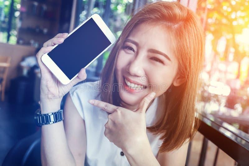 Asiatisk flicka för skönhet som ler och visar smartphonen royaltyfri bild