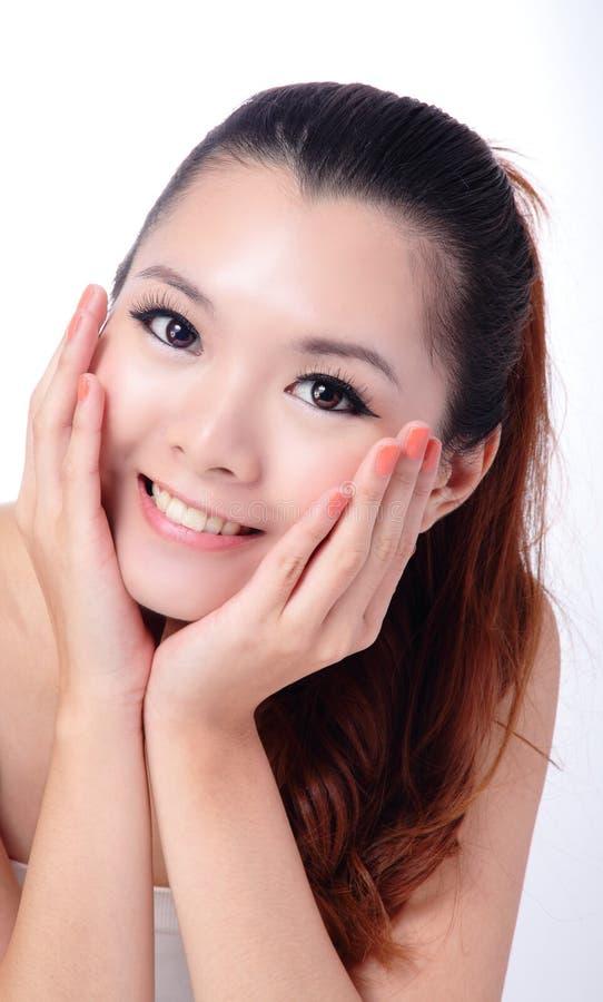 Asiatisk flicka för skönhethudomsorg som trycker på henne framsida royaltyfri foto