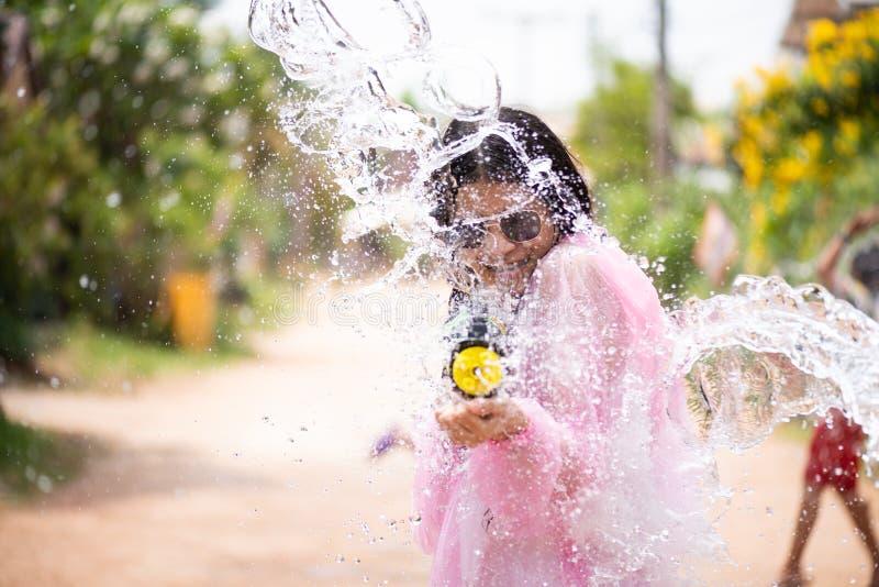 Asiatisk flicka för ung lycklig skönhet med skjortan för sommar för vattenvapen den bärande i den Songkran festivalen - vatt royaltyfri foto