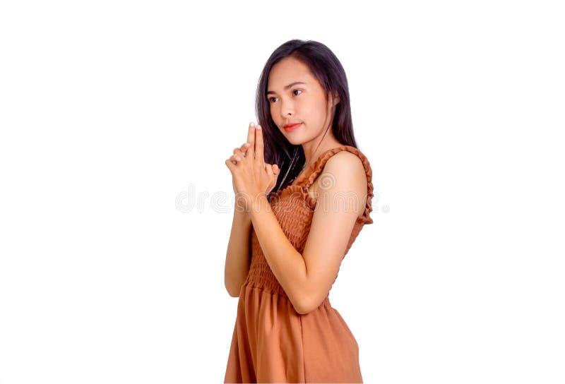 Asiatisk flicka i brun gest för ärmlös tröjavisningvapen med hennes händer royaltyfria bilder