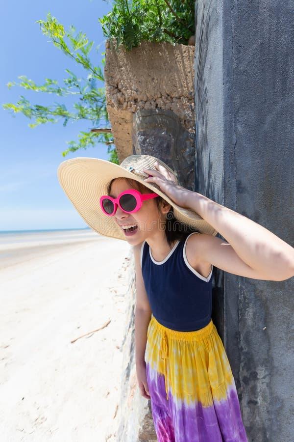 Asiatisk flicka i solglasögon och hatten som tycker om havssiktsdurinen royaltyfri fotografi