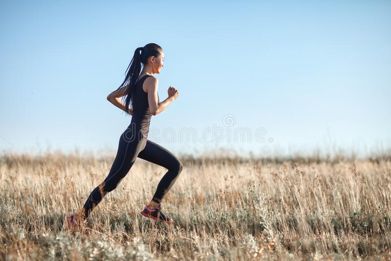 Asiatisk flicka i sportswear som stöter ihop med fältet, morgongenomkörare arkivbild