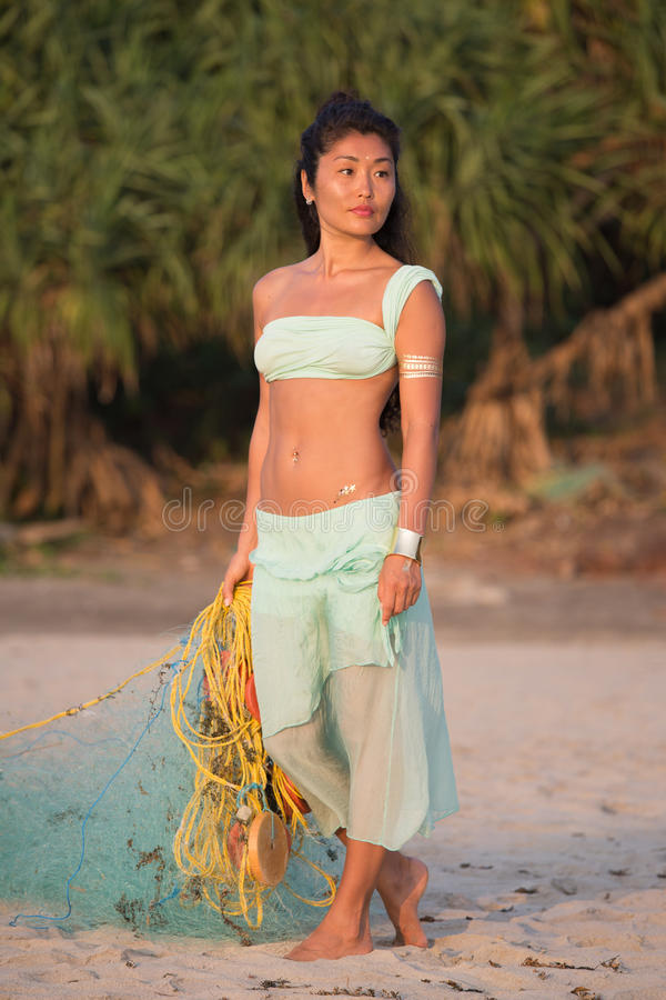 Asiatisk flicka med ett fisknät på stranden royaltyfri foto