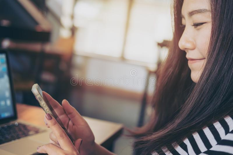 Asiatisk flicka med smileyframsidan genom att använda den smarta telefonen med bärbara datorn på trätabellen i modernt kafé fotografering för bildbyråer