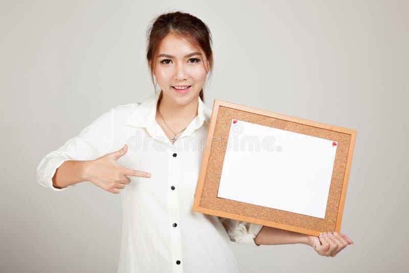 Asiatisk flicka med stiftet för tomt papper på korkbräde arkivfoton