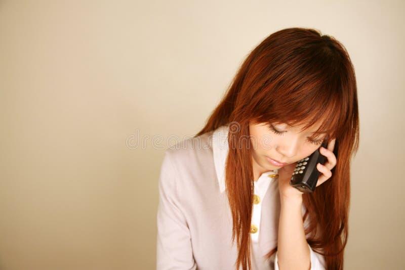 Asiatisk flicka med telefonen royaltyfria foton