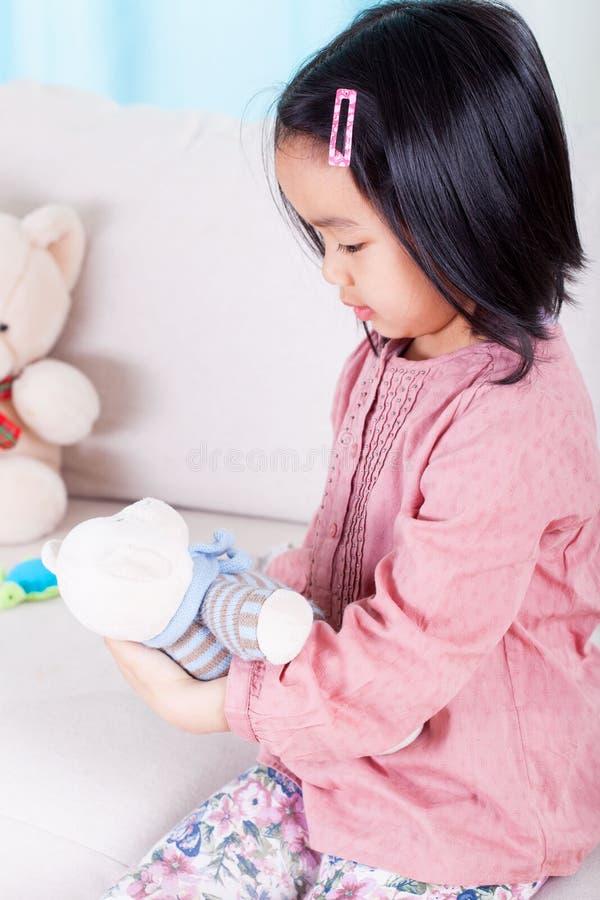 Asiatisk flicka och hennes nallebjörn royaltyfria foton