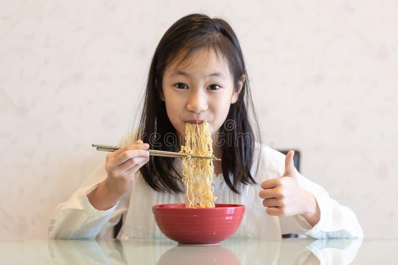 Asiatisk flicka som äter nudlar på tabellen arkivbild