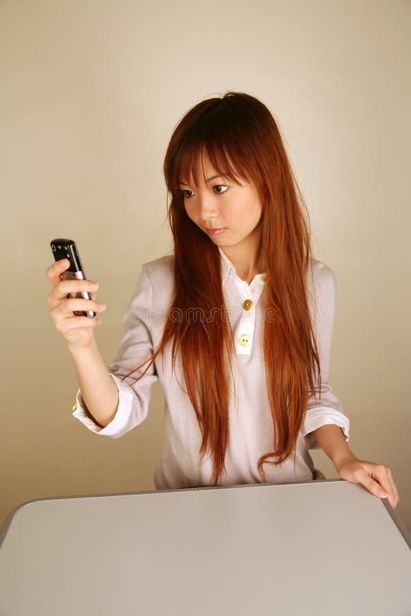 Asiatisk flicka som använder hennes mobiltelefon arkivfoto