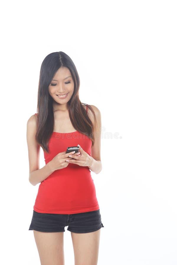 Asiatisk flicka som använder mobiltelefonen royaltyfri bild