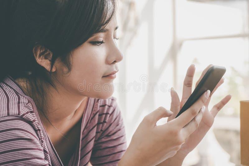 Asiatisk flicka som använder mobiltelefonen vid fönster arkivbilder