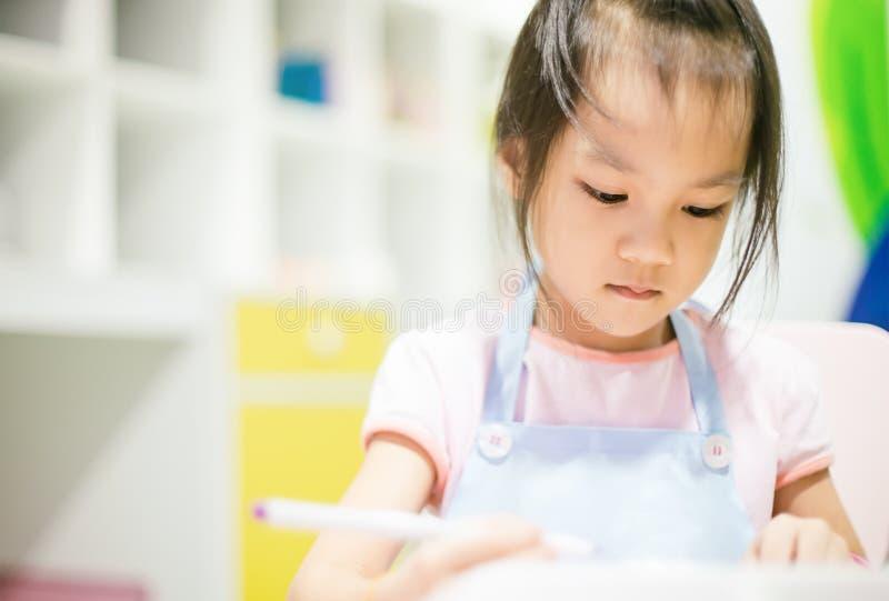 Asiatisk flicka som bär ett förkläde som lär konst royaltyfria bilder