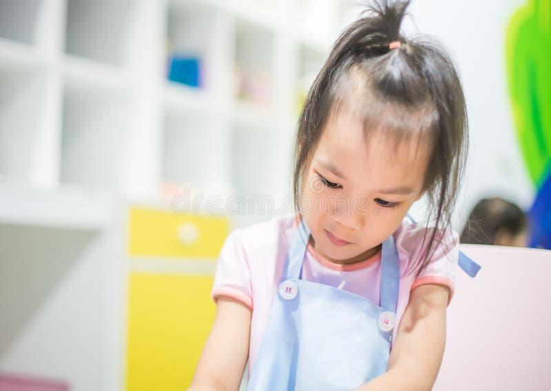 Asiatisk flicka som bär ett förkläde som lär konst arkivbild